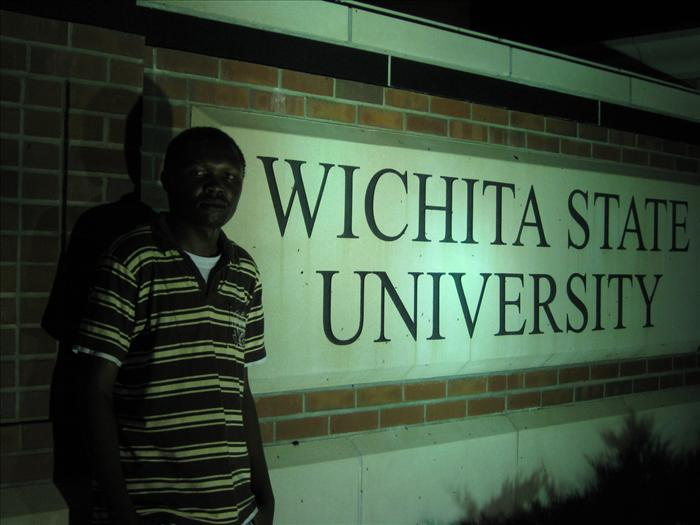 Gideon Maiyo posing at the entrance of Wichita State University-Photo from his Graduates.com profile