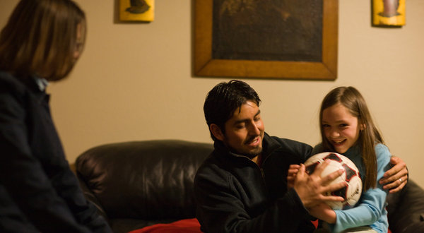 Raúl and Judy Cárdenas playing with their 8-year-old daughter, Pamela, in their home in Denver.
