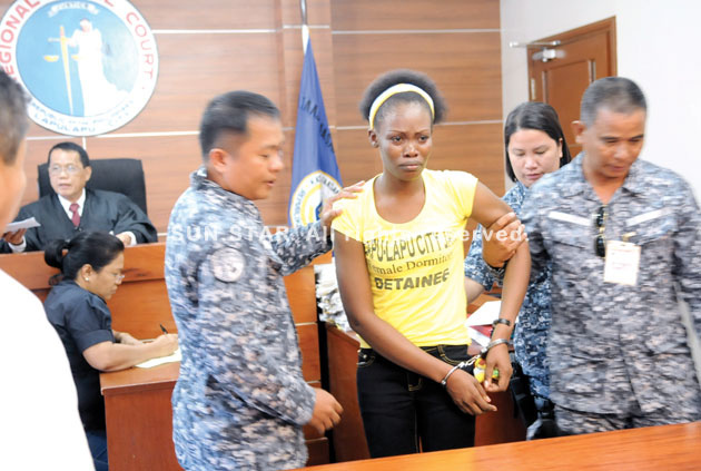 CEBU. Bureau of Jail Management and Penology personnel escort Kenyan national Asha Atieno Oguto after the court, presided by Judge Toribio Quiwag (background), finds her guilty of transporting illegal drugs into the country. (Allan Cuizon)