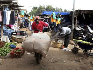 A man pushes a wheelbarrow through Nairobi