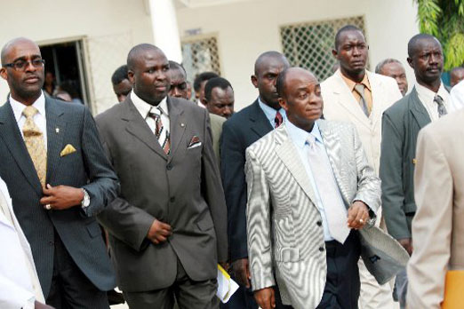 Super-rich Nigerian televangelist Bishop David Oyedepo (right, in gray jacket) sorrounded by aides and supplicants.