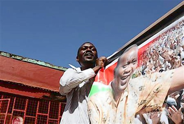 A supporter of Finance minister Uhuru Kenyatta holds a poster during a solidarity walk through Gatundu town, north of Nairobi