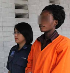 Judith (right) escorted by Customs personnel to a courtroom yesterday.
